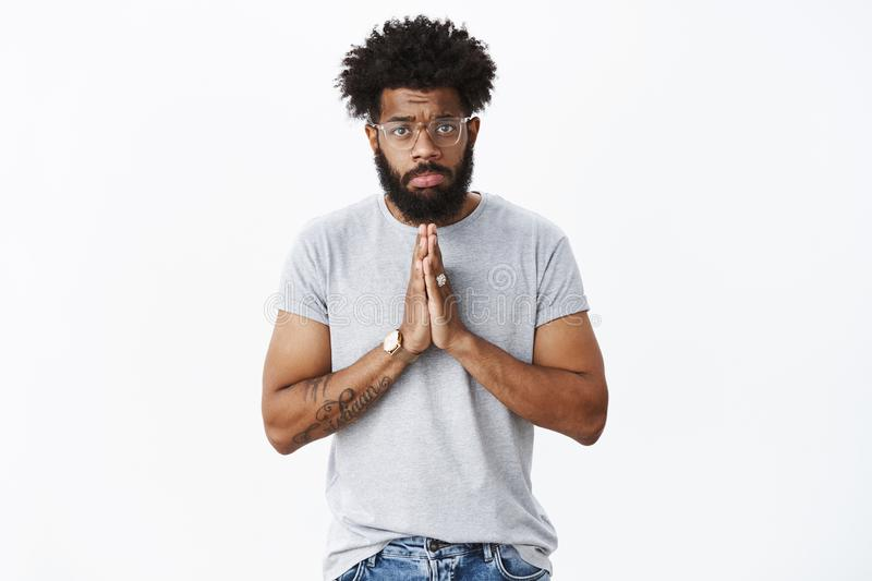 Sad and gloomy african american guy with pierced nose, tattoos wearing glasses pouting upset holding hands in pray over. Chest, frowning begging for mercy and royalty free stock photo