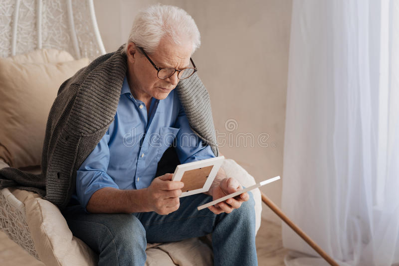 Sad gloomy man holding old photos. Pictures from the past. Sad gloomy unhappy man sitting in the armchair and holding old photos while remembering his youth stock photos