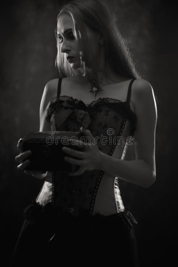 Sad gothic girl. With chest posing over dark background stock image