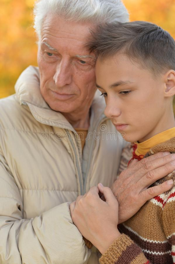 Close up portrait of sad grandfather and grandson hugging in park royalty free stock photos