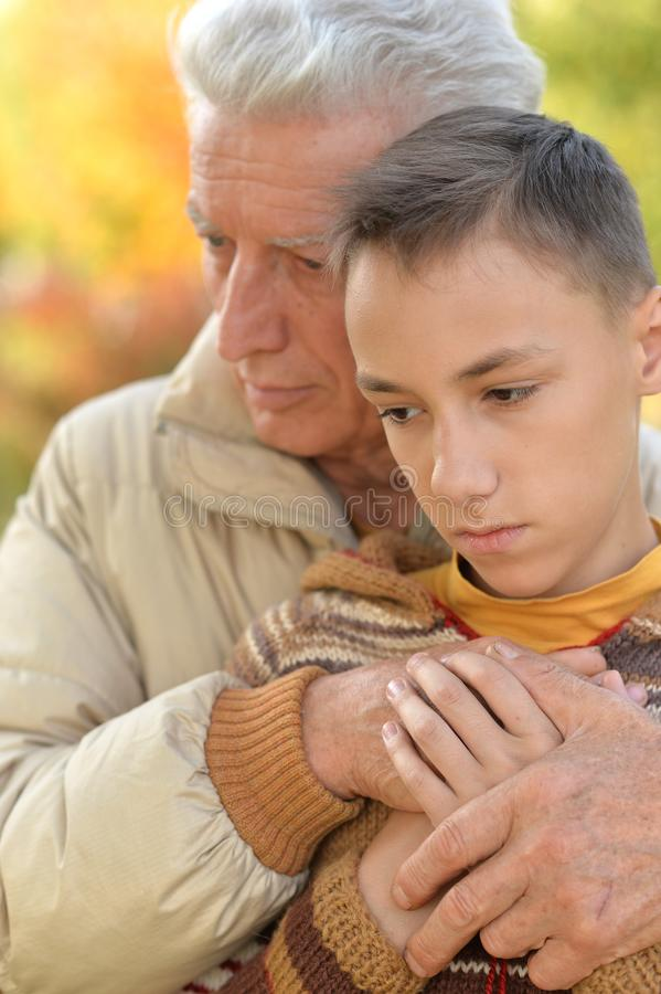 Sad grandfather and grandson stock images