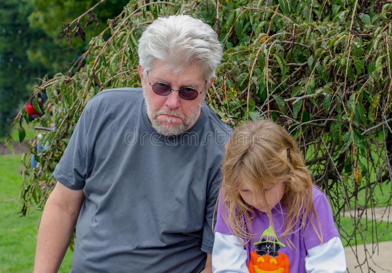 Sad grandpa and child pouting. Grandpa and granddaughter are  pouting and sad their fun day has to end, and it`s time to go home royalty free stock photo