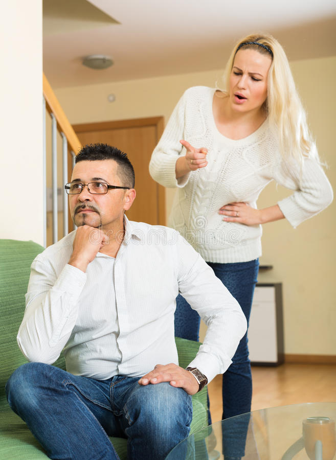 Sad guy and angry woman during quarrel. Family quarrel. Sad guy and angry women during quarrel at home stock images