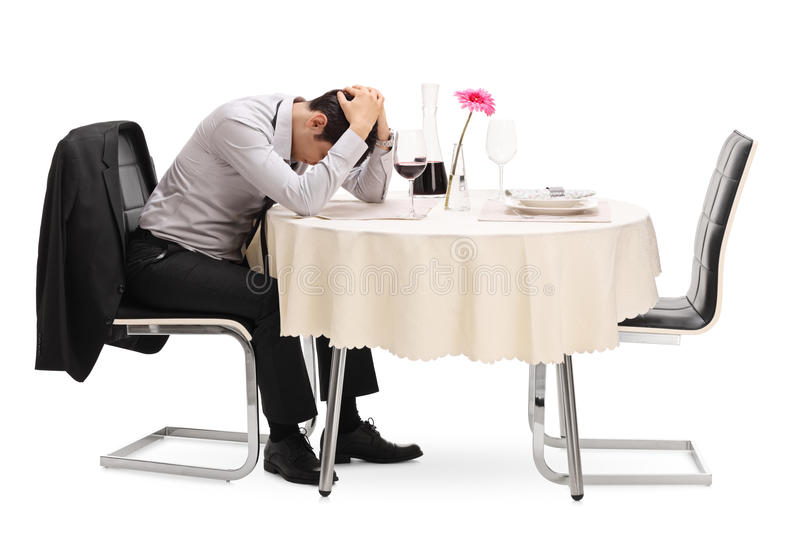 Sad guy sitting alone at a restaurant table. Desperate guy sitting alone at a restaurant table with his head down isolated on white background stock image