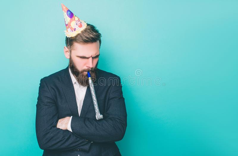 Sad guy is standing and looking down. He is upset. Man is holding a wistle in his mouth and has a birthday hat on the. Head. Isolated on blue background royalty free stock images
