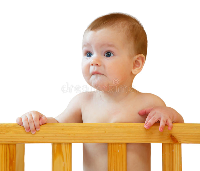 Sad half-year-old baby holding the side cot stock photo