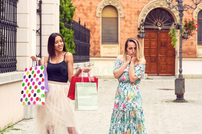 Sad and happy women at shopping royalty free stock image