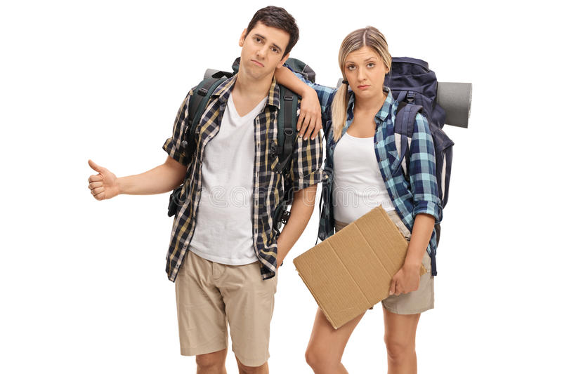 Sad hikers holding a blank cardboard sign and hitchhiking. Isolated on white background stock images