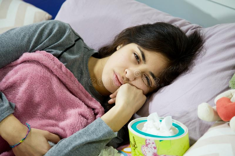 Sad ill woman laying in bed unhappy royalty free stock photos