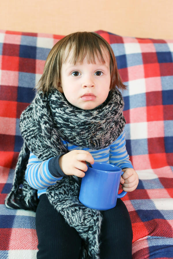 Sad ill 2 years child in warm woolen scarf with cup of tea stock photography