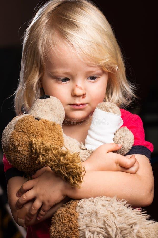 Sad injured boy with stuffed dog toy stock image