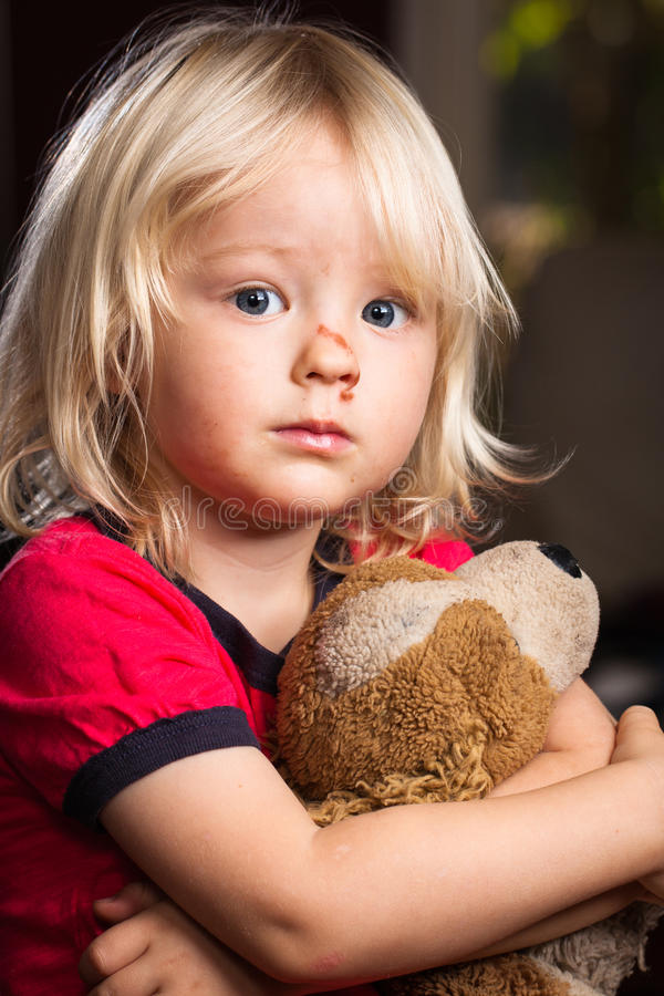 Sad injured boy with stuffed toy stock photography