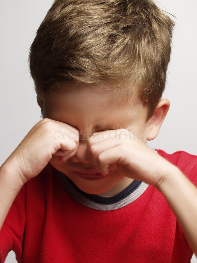 Sad kid. Exhausted and sad little kid portrait,rubbing his eyes stock photo