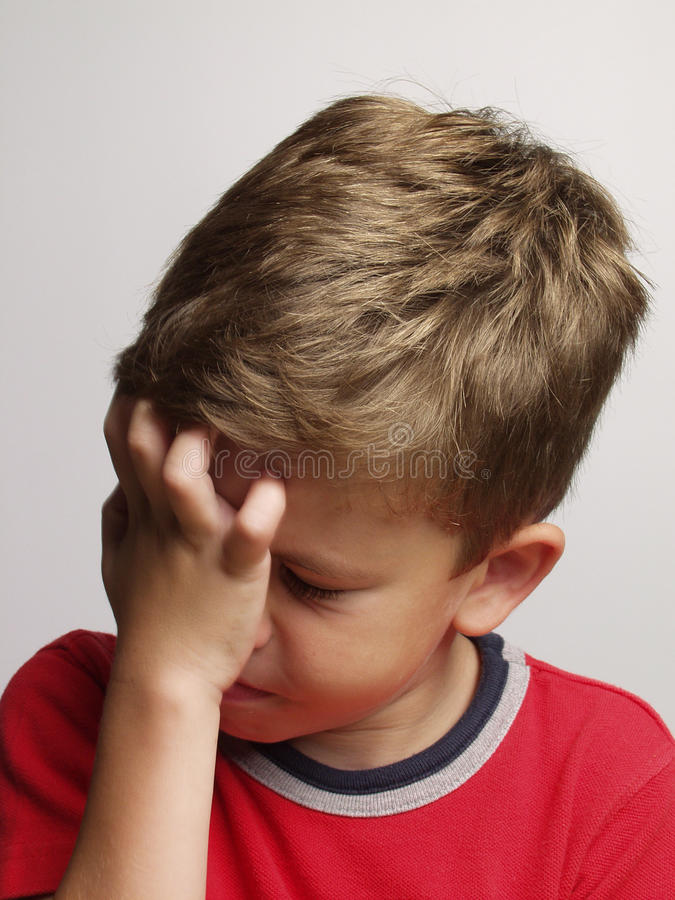 Sad kid. Exhausted and sad little kid portrait,rubbing his eyes royalty free stock images