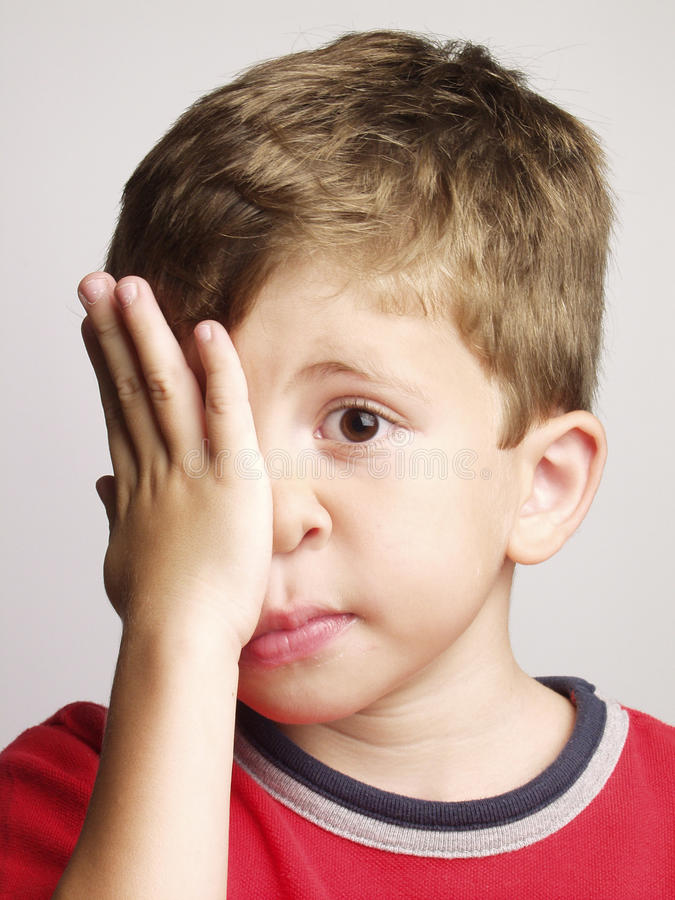 Sad kid. Exhausted and sad little kid portrait,rubbing his eyes stock images