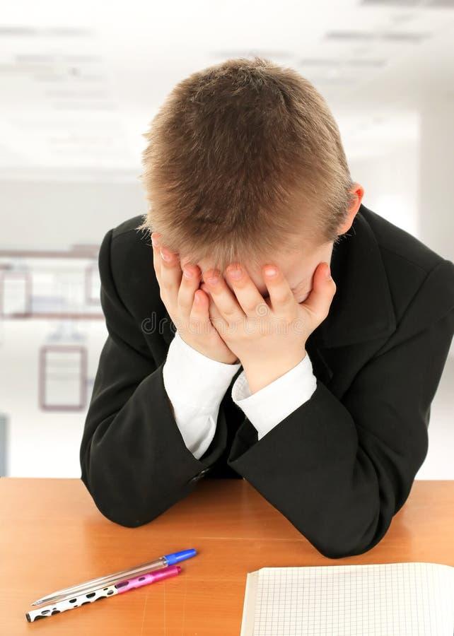 Sad Kid at the Desk royalty free stock image