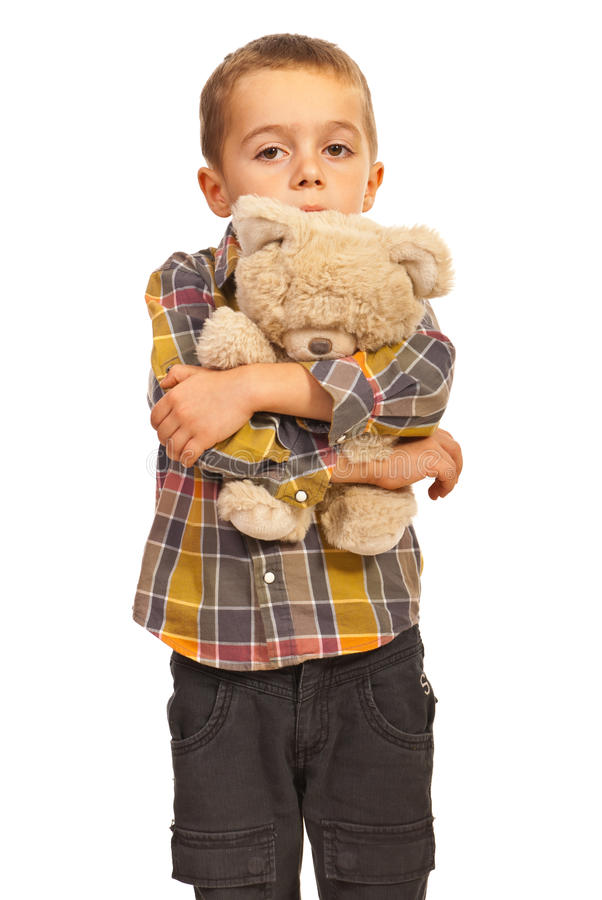 Sad kid hugging teddy stock photos