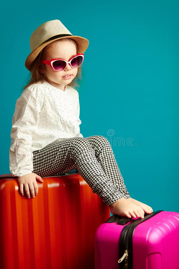 Sad kid sitting on suitcases, frustrated little girl in straw hat and sunglasses is in a bad mood, portrait on isolated royalty free stock images