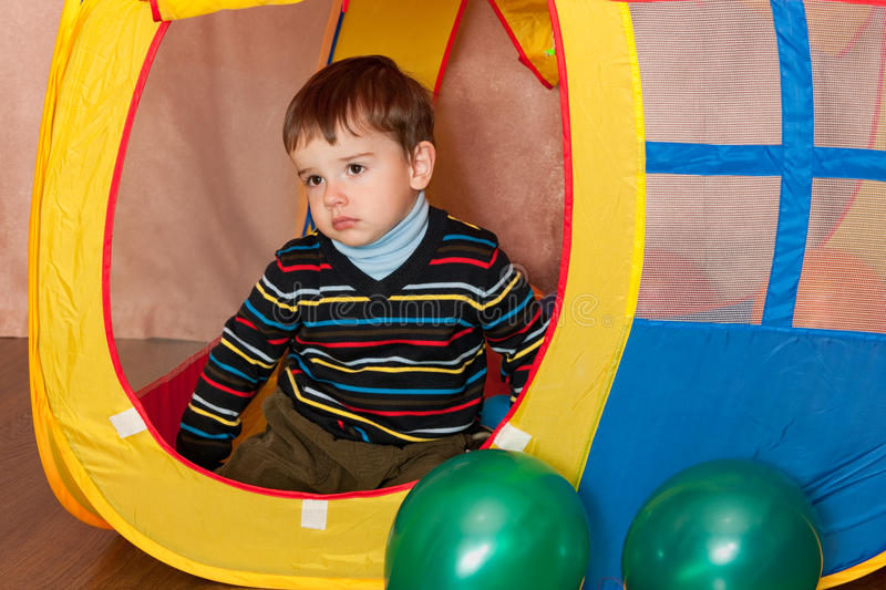 Sad kid in a toy house. A thoughtful little boy is sitting in a yellow toy house stock photography