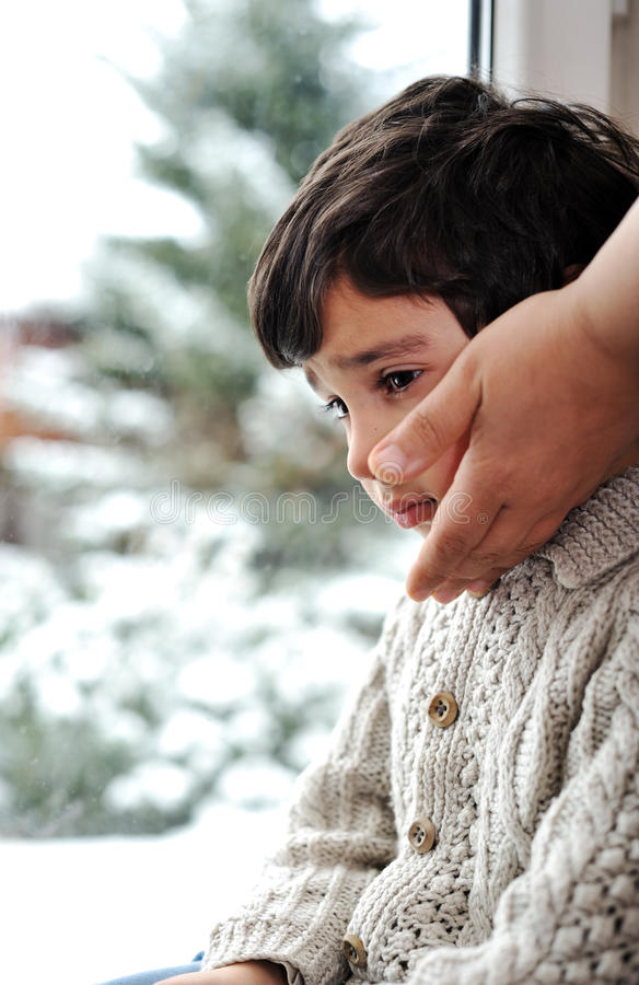 Sad kid on window and winter snow stock photos