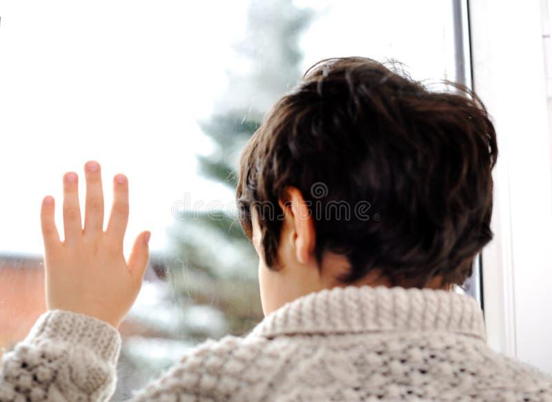 Sad kid on window and winter snow