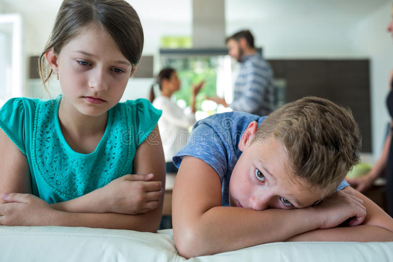 Sad kids leaning on sofa while parents arguing in background. At home stock images