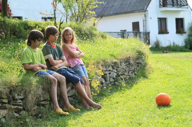 Sad kids on stone wall. Little kids- two sad boys and one girl sitting on stone wall on grass with football ball lying in front of them stock photography
