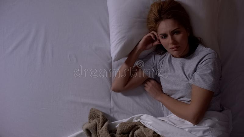 Sad lady awakening alone in bed at night, thinking about divorce, depression. Stock photo royalty free stock images