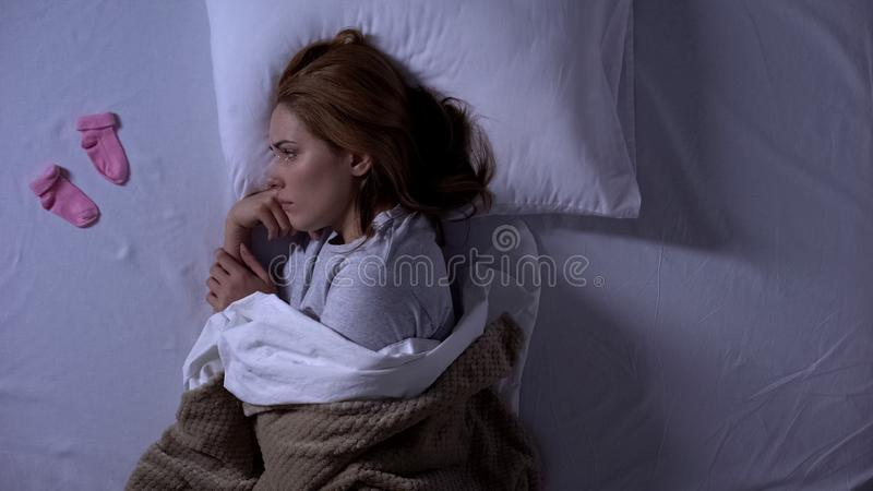 Sad lady crying lying in bed and looking at baby socks near pillow, miscarriage. Stock photo royalty free stock photos