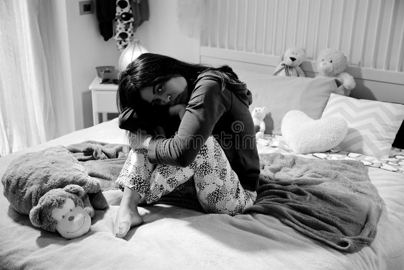 Sad latino girl sitting in bed thinking black and white stock photos
