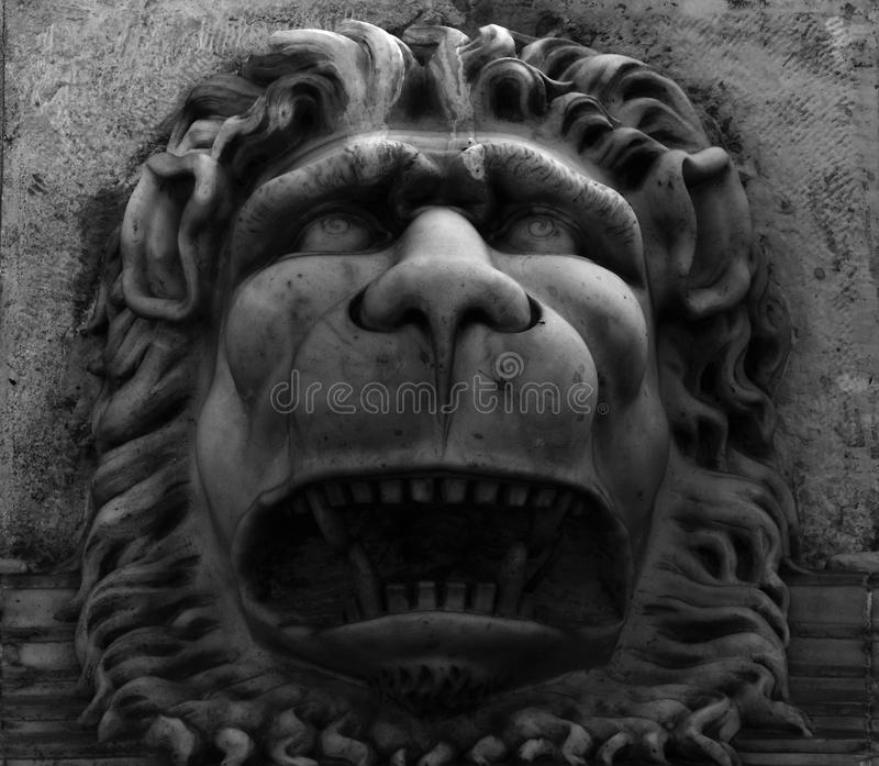 The sad lion. Shot in black and white, detail on an sculpture representing a lion placed on the facade of this historic building, set in Born, Barcelona, Espa stock images