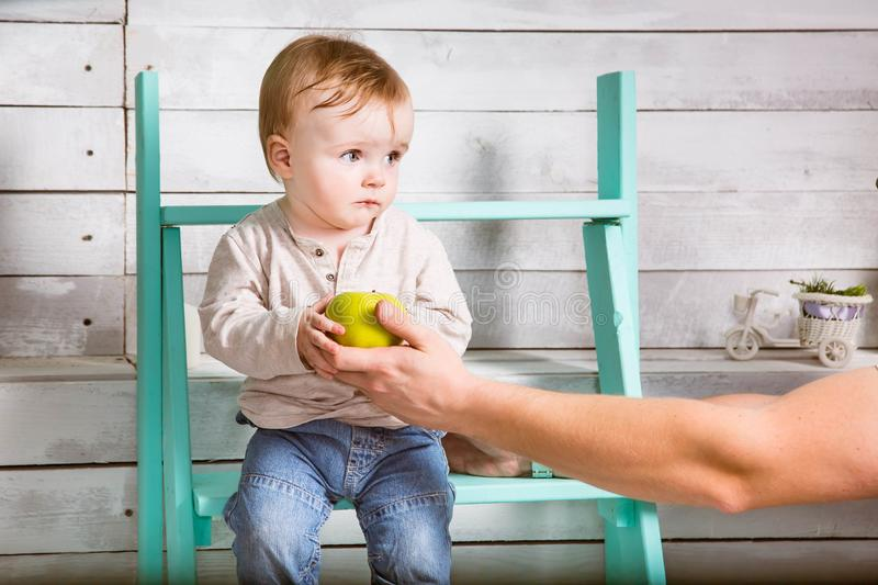 Sad little baby boy take an apple from father. He sits on the steps indoor. White wooden background stock photo