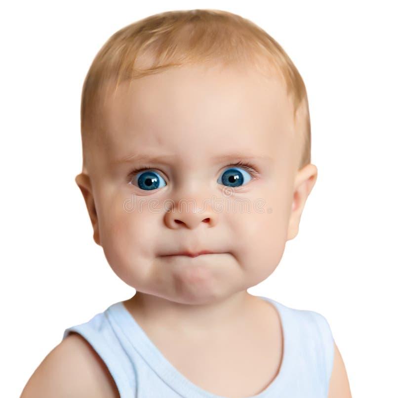 Sad little baby isolated on a white background. Sad little blue-eyed redhead baby isolated on a white background royalty free stock image