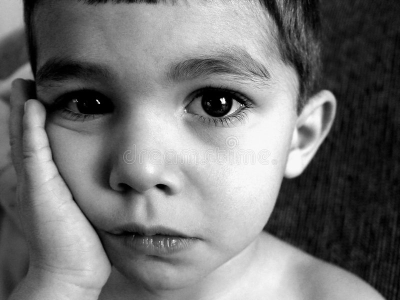 Sad Little Boy. Little boy with hand to face looking very sad, grain, black and white stock photo