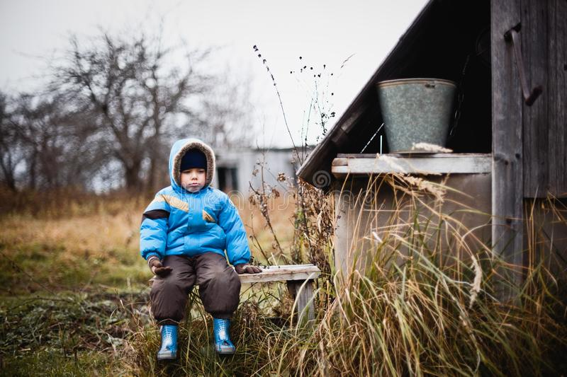 Sad little boy in a blue jacket and brown pants sitting on the bench. Next to the wooden structure. Gloomy day in the village. royalty free stock photography