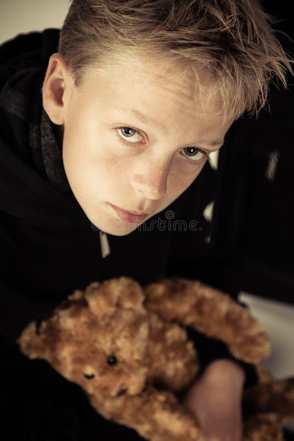 Sad little boy holding plush bear toy stock photo