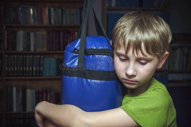 Sad little boy hugs a punching bag stock photography