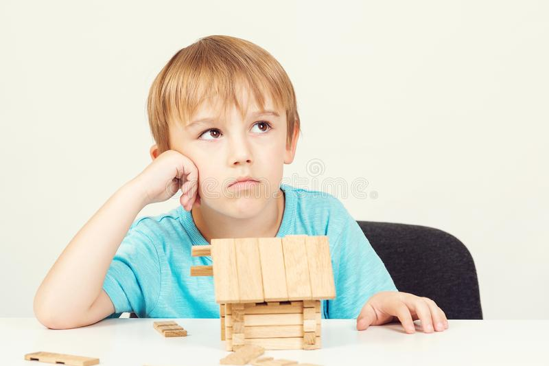 Sad little boy sit at table. Kid dreams about own home, family. Boy cann`t build small wooden house.  royalty free stock image
