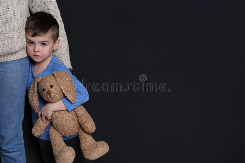 Sad little boy with toy hugging his mother on black background stock images