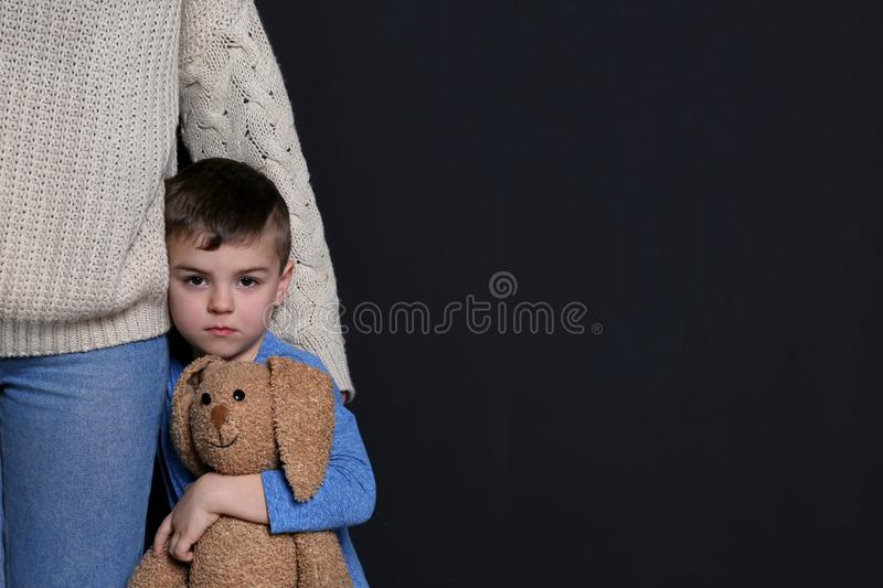 Sad little boy with toy hugging his mother on black background stock photography