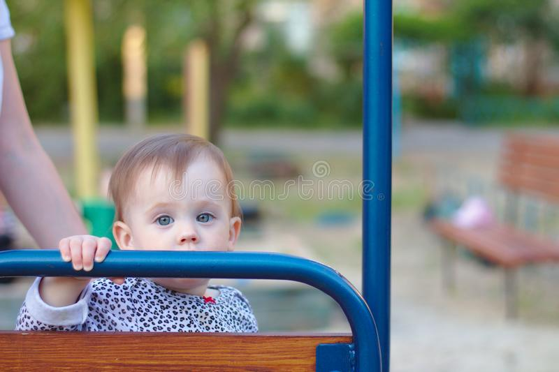 Sad little child is sitting on the swing on the playground and looking forward. Swinging, summer, outside, activity, dream, imagination, ride, toddler, girl stock images
