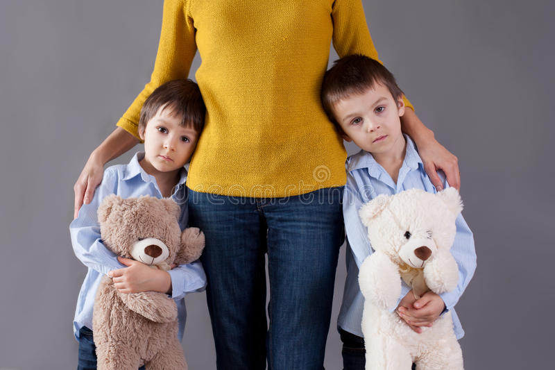 Sad little children, boys, hugging their mother at home, isolate stock photos