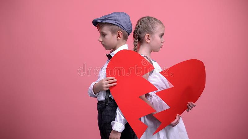 Sad little couple holding broken pieces of red heart, quarrelling, brake up stock images