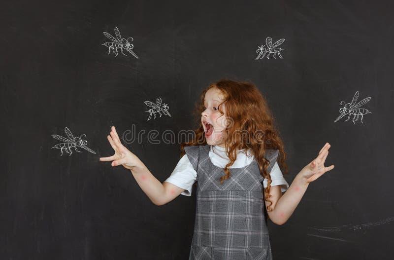 Sad little girl afraid of bites mosquitoes. Flying around her stock image