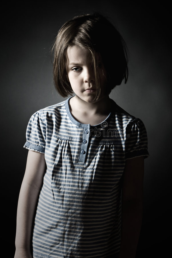 Sad Little Girl against Grey Background. Low Key Shot of a Sad Little Girl against Grey Background stock photography