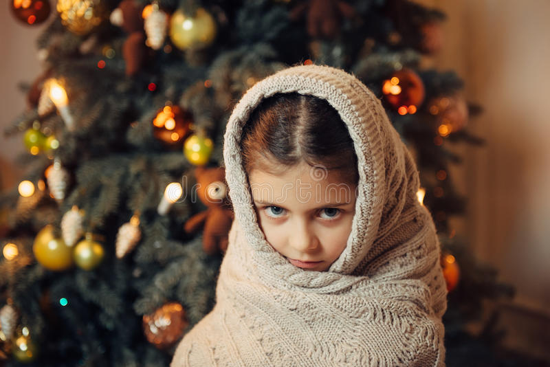 Sad little girl covered in warm scarf waiting for gift royalty free stock photography