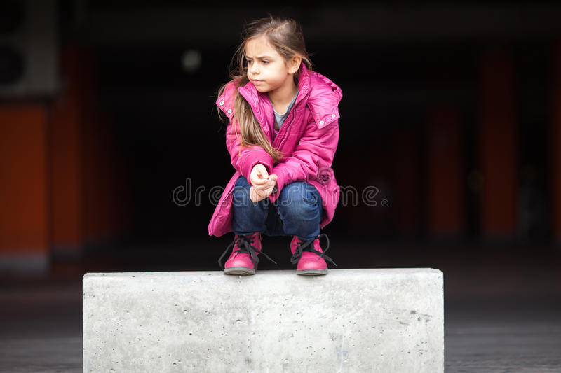 A sad little girl crouching down. In pink royalty free stock images