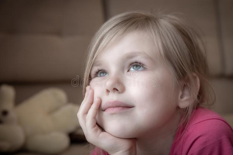 Sad little girl feels lonely laying on a floor and looking in window royalty free stock photography