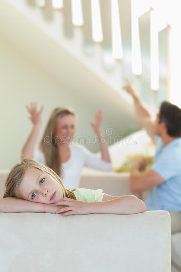 Sad little girl with fighting parents behind her stock image