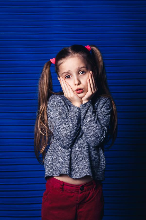 Sad little girl holding her cheek on a blue background. child toothache concept. stock photo